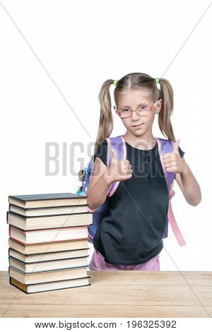 Schoolgirl in glasses with backpack shows two hands thumbs up, standing at a wooden desk with a stack of books, isolated on white background
