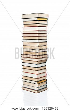 High stack of various books stacked one on another, isolated on white background