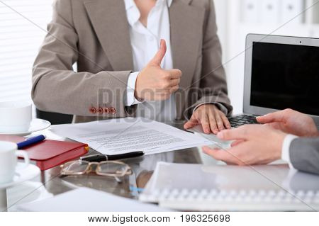 Group of business people or lawyers at meeting discussing contract papers. Woman showing thumb up.