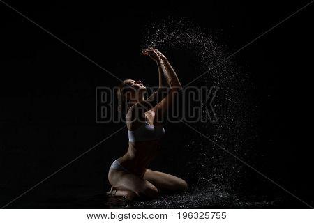 Young happy girl enjoying water splashes posing in dark studio