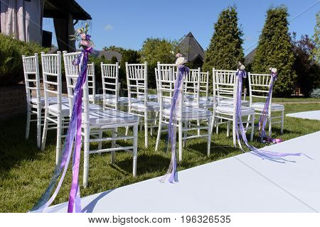 Decoration of the white chairs with Eustoma flowers and ribbons for exterior wedding ceremony