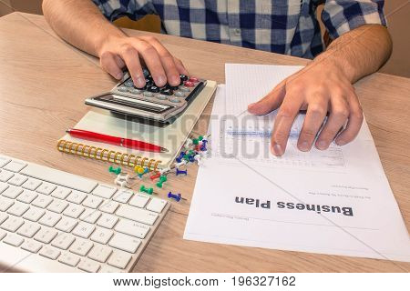 Businessman working on office desk with Calculator. accounting concept. Financial report values with dollars calculator - color / Old Polaroid