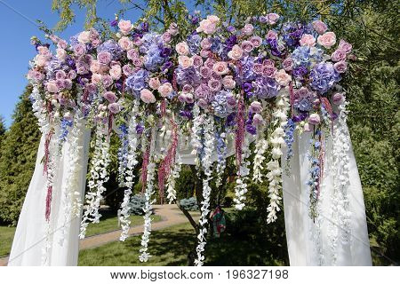 Decorated wedding arch with violet, blue, pink and white flowers for the wedding ceremony