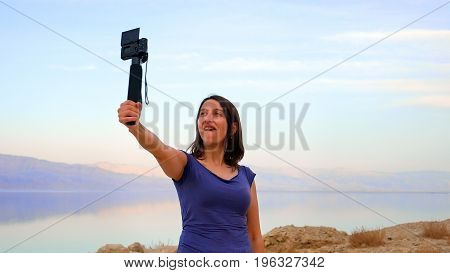 Brunette longhair woman takes a selfie with camera at the mountain lake. Summer day recreation activity.