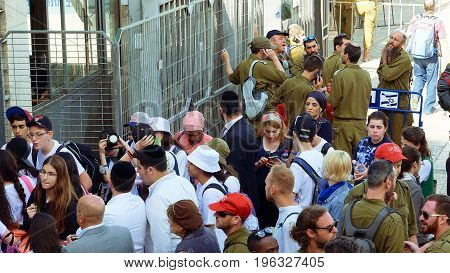 Jerusalem, Israel - May 25, 2017: People crowd with soldiers and military men entering to Western wall square in Jerusalem. Western wall or Wailing wall or Kotel is the most sacred place for all jews.