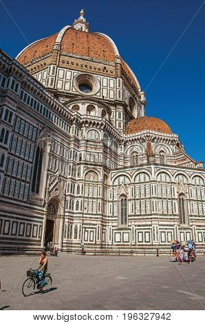 Florence, Italy - May 14, 2013. View of woman on bicycle next to the Cathedral Santa Maria del Fiore. In the city of Florence, the famous and amazing capital of the Italian Renaissance. Tuscany region