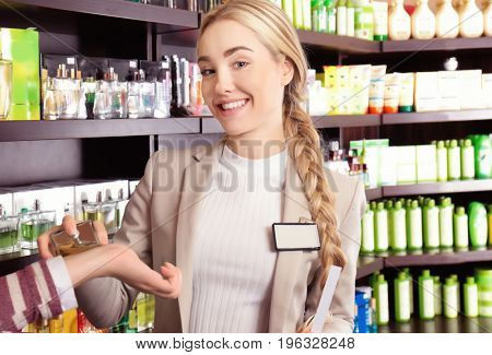Assistant helping young woman in perfumery