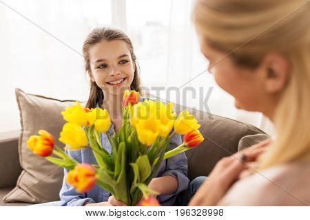 people, family and holidays concept - happy girl giving tulip flowers to her mother at home