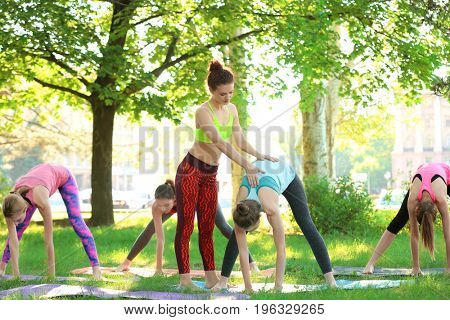 Instructor helping people to practice yoga outdoors