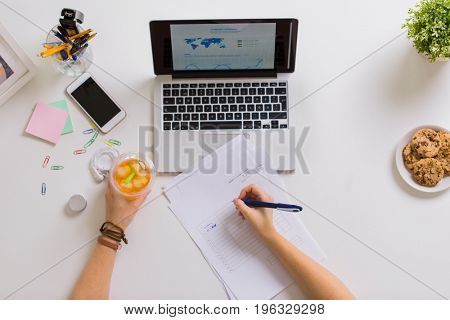 business, accounting and freelance concept - woman hands with papers, cup of drink and laptop computer working at office table