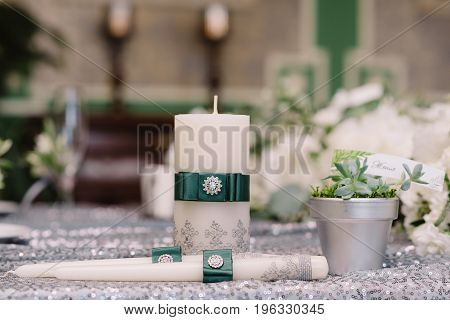 Wedding decorated white candles with the silver brooch and green ribbons next to silver pot with guest's name
