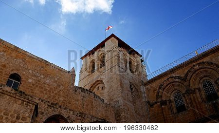Roof of the Holy Sepulcher Church in Jerusalem with flying flag. The Holy Sepulchre Church and Empty Tomb the most sacred places for all religious Christians in the world. Calvary also located there.