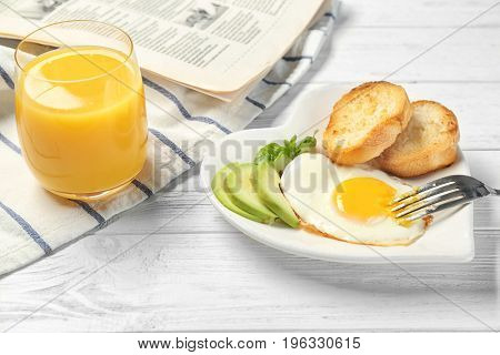 Delicious over easy egg with toasts and avocado on kitchen table