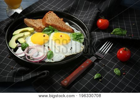 Delicious over easy eggs with toasts, onion and avocado on kitchen table