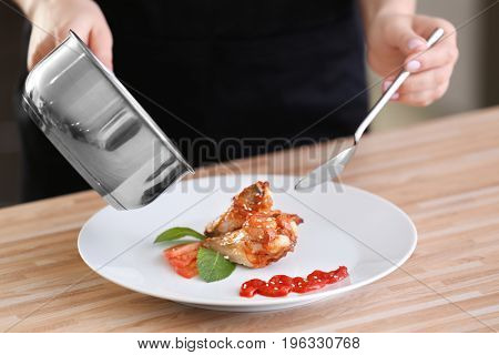 Woman pouring yummy fried chicken with sauce on white plate