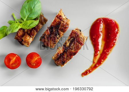 Delicious grilled spare ribs with cherry tomatoes and spicy sauce on white plate, top view