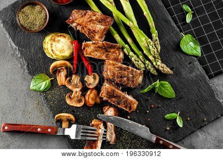 Delicious grilled spare ribs with vegetables on black slate plate
