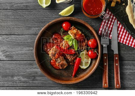 Delicious grilled spare ribs with vegetables and sauce in bowl on wooden table