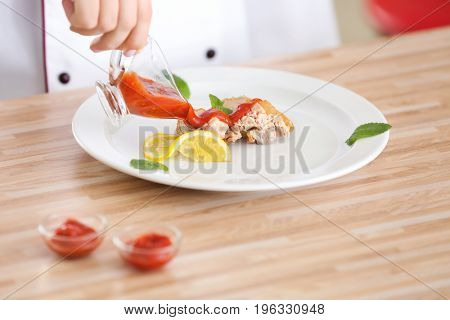 Woman pouring yummy fried chicken thigh with sauce on white plate