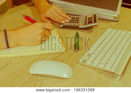 Business executive woman at workplace. Businesswoman Calculating Tax At Desk In Office - Retro color