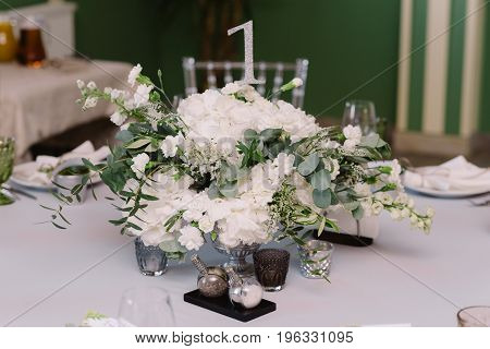 White floral decoration for the guests table on the white cloth with number
