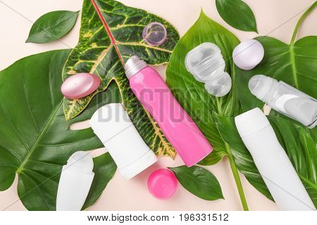 Different deodorants with leaves on light background