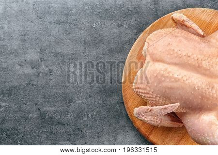Wooden board with whole raw turkey on grey background