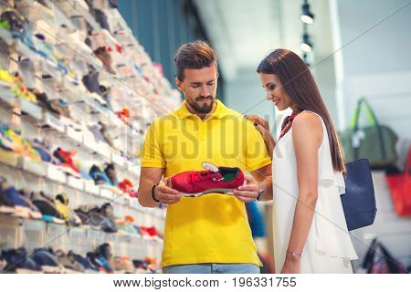Happy couple in shopping mall visit store