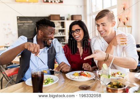 leisure, food and people concept - group of happy international friends eating and having fun at restaurant table