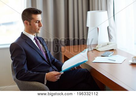 business, people and paperwork concept - businessman with papers in folder working at hotel room