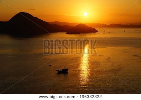 Orange sunrise view from Padar Island part of komodo national park with little silhouette boat in the ocean Flores Indonesia.