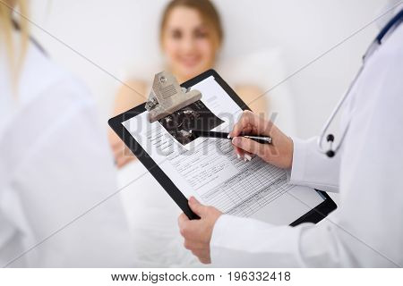Close-up of a female doctor holding application form while consulting patient.