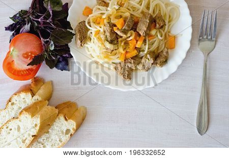 spaghetti tomato and rosemary bread and a fork on white background