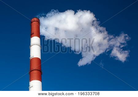 Heat and power central smoke industrial chimney against clear blue sky