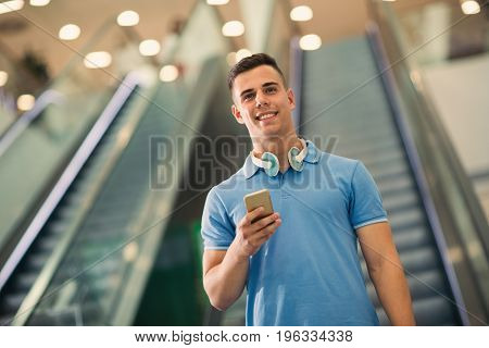 Handsome guy holding mobile phone and smiling while walking down the mall