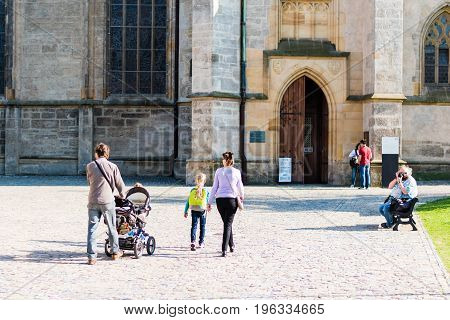 KUTNA HORA CZECH REPUBLIC - MAY 21 2017: The tourists in front of entrance to the Saint Barbara's Church.