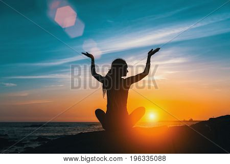 Yoga silhouette meditation girl on the sea during amazing sunset.