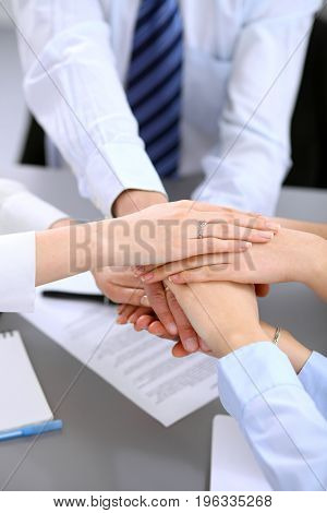 Business people group joining hands and representing concept of friendship and teamwork