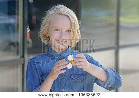 Beautiful cheerful school girl playing with a gold fidget spinner. A popular toy for children and adults.