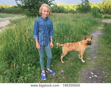 Cheerful girl walks with a dog mongrel