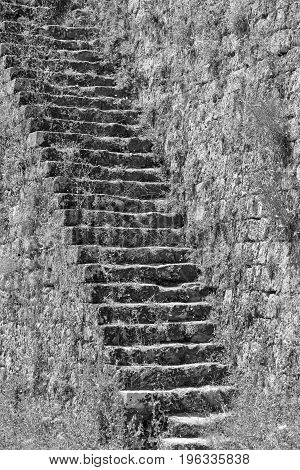 old stone ladder on an ancient stone wall of fortress closeup monochrome tone