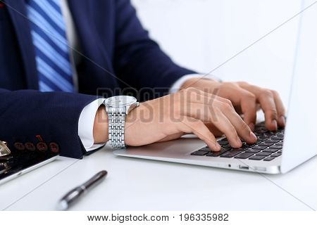 Young man working with laptop computer, man's hands on notebook, business person at workplace.
