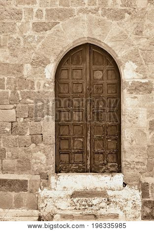 old wooden door on an ancient stone wall of color sepia