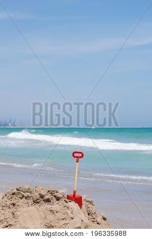 Red shovel on the sand in the beach