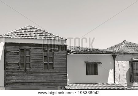 facades of old small houses close up against the background of empty sky monochrome tone