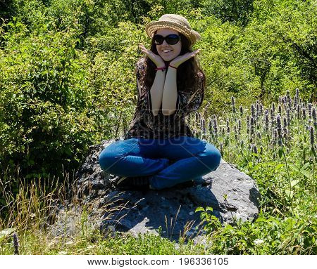 Smiling young girl with sunglasses and hat sitting on the rock