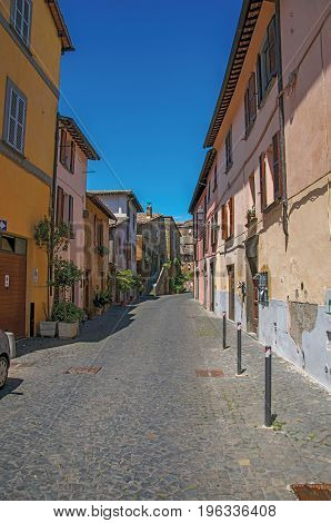 Overview of an alley with old buildings and garage under a sunny blue sky, at the town of Orvieto, a pleasant and well preserved medieval city. Located in Umbria, central Italy