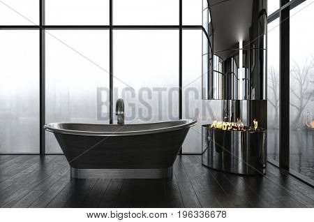 Luxury bathroom with a dark boat-shaped freestanding bathtub in front of large windows overlooking a misty winter scene with a fire burning in the corner of the room