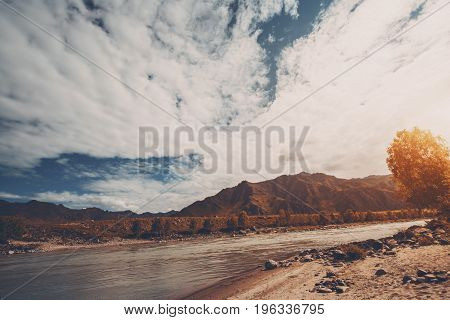 Wide angle view of Katun mountain river on morning with mountains and hills in background dark blue sky with cloudscape birch and stony shore on the right Altai Kuyus district Russia