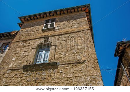 View of the facade of an old stone building, under a sunny blue sky, in an alley of Orvieto, a pleasant and well preserved medieval city. Located in Umbria, central Italy
